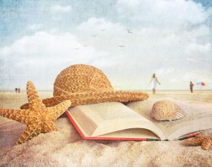 Straw hat , book and seashells in the sand