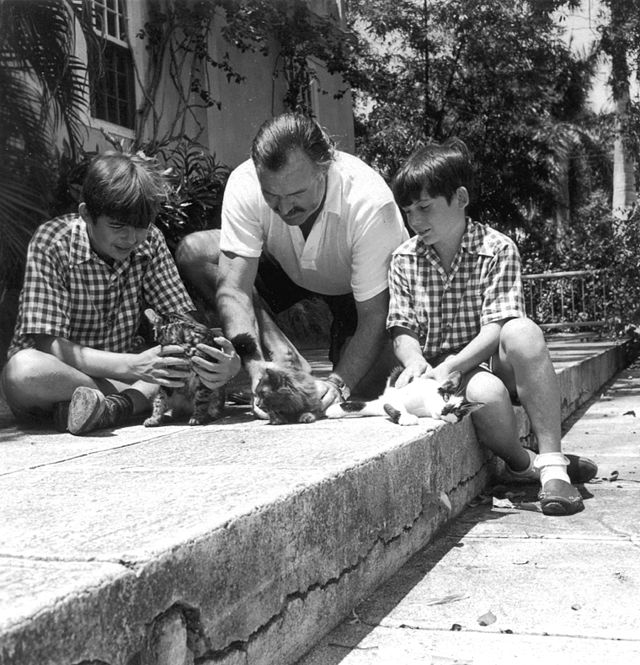 Ernest Hemingway and his sons playing with kittens.