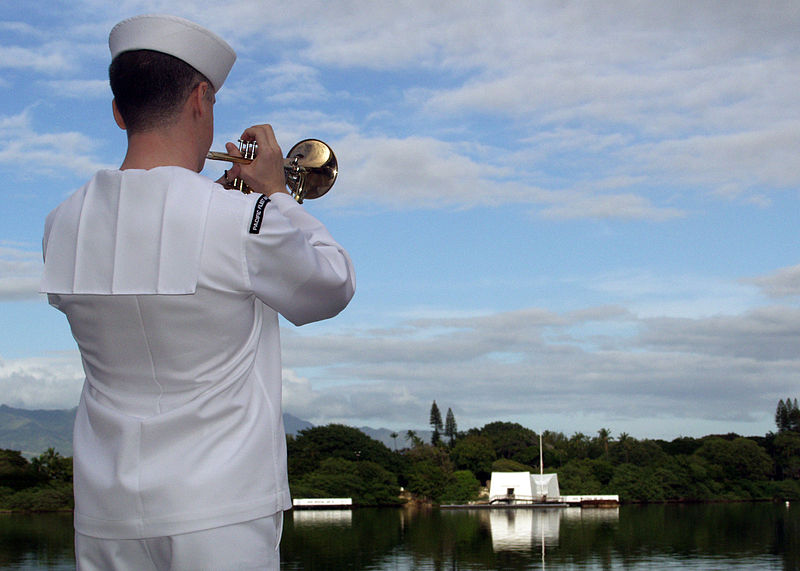 "Image by U.S. Navy photographer, MCC David Rush. ""A Sailor from the U.S. Pacific Fleet Band plays taps during a joint U.S. Navy/National Park Service ceremony commemorating the 67th anniversary of the attack on Pearl Harbor. The theme of this year's historic commemoration, ""Pacific War Memories: The Heroic Response to Pearl Harbor,"" emphasized the brave efforts of those who fought at sea, on land and in the air to turn the tide in the Pacific. More than 2,000 distinguished guests and the general public joined service members, Pearl Harbor survivors and their families and friends for the annual observance."" Image description via Wikimedia Commons."