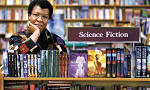 Octavia E. Butler with science fiction book shelf