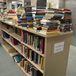 books rescued from flood piled on other shelves
