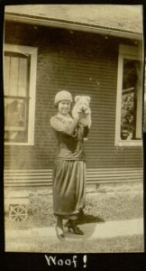Photo of woman holding up a small dog on her shoulder
