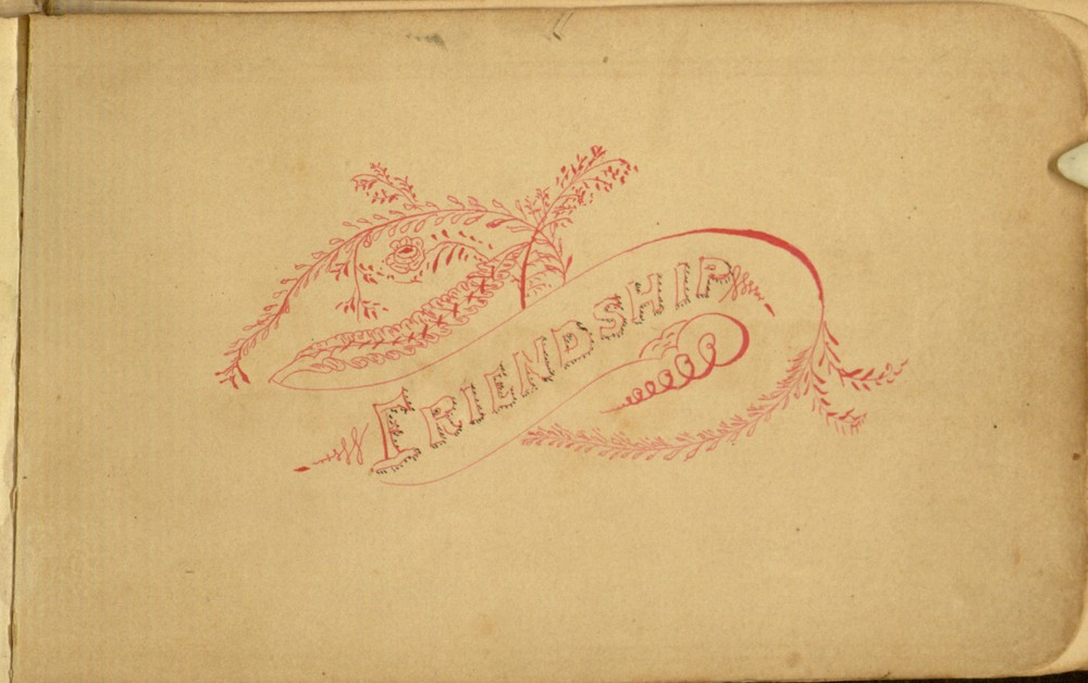 "Decorative ink-work in red around the word ""Friendship."""