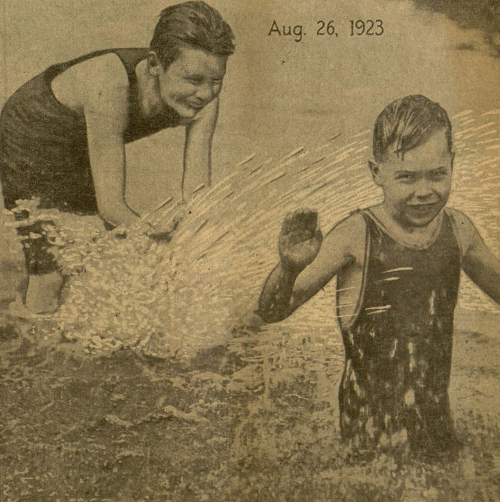 Two young boys playing in a body of water.