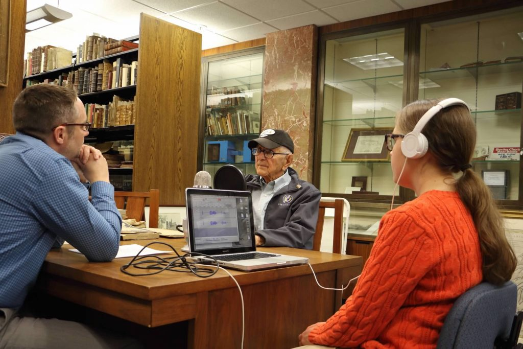 Photo of 2 men and 1 woman seated around a table. The two men are talking and the woman is recording them with a microphone and laptop.