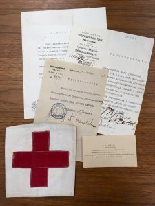 Photo of 3 paper documents in Russian, a calling card (also in Russian), and a Red Cross arm band.