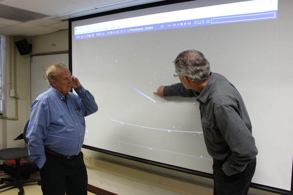 Astronomy professors pointing at a projection of the night sky.