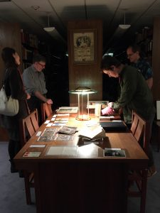 Four people looking at books on a table.
