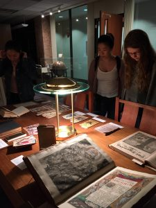 Three students looking at books on a table.
