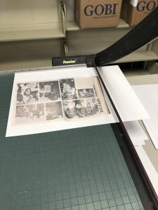 A print being cut with paper cutter.