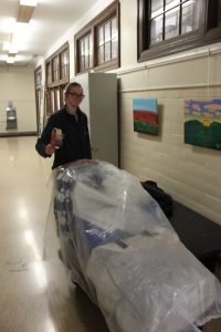 Student moving a cart of archival material