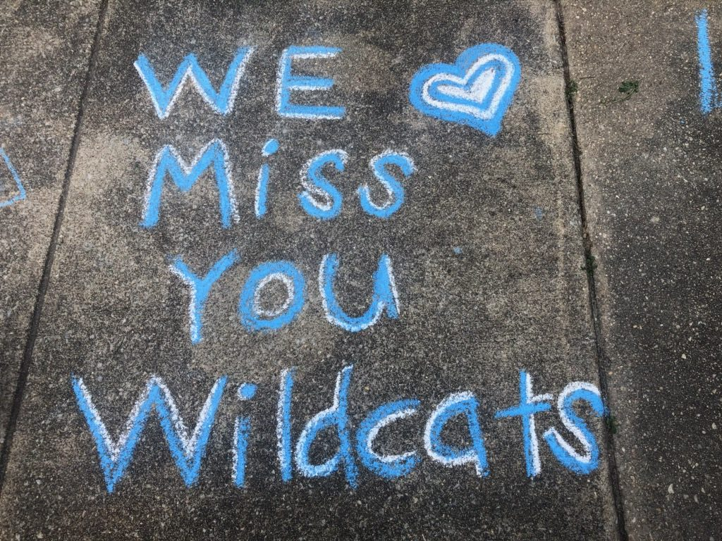 We miss you Wildcats drawn in chalk on sidewalk.