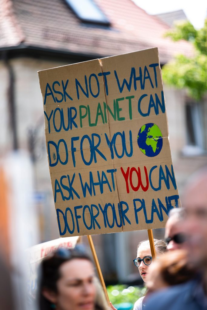 """Protesters holding a sign that says """"ask not what your planet can do for you. Ask what you can do for your planet"""""""