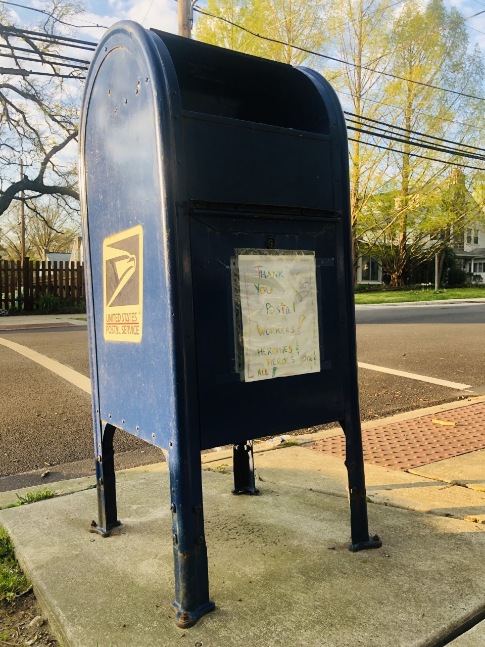 Image of a US postal drop box with a hand drawn letter from a child thanking postal workers for their service.