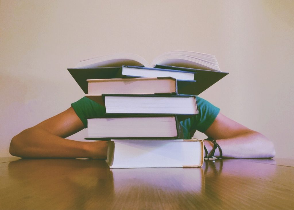 student sitting behind books