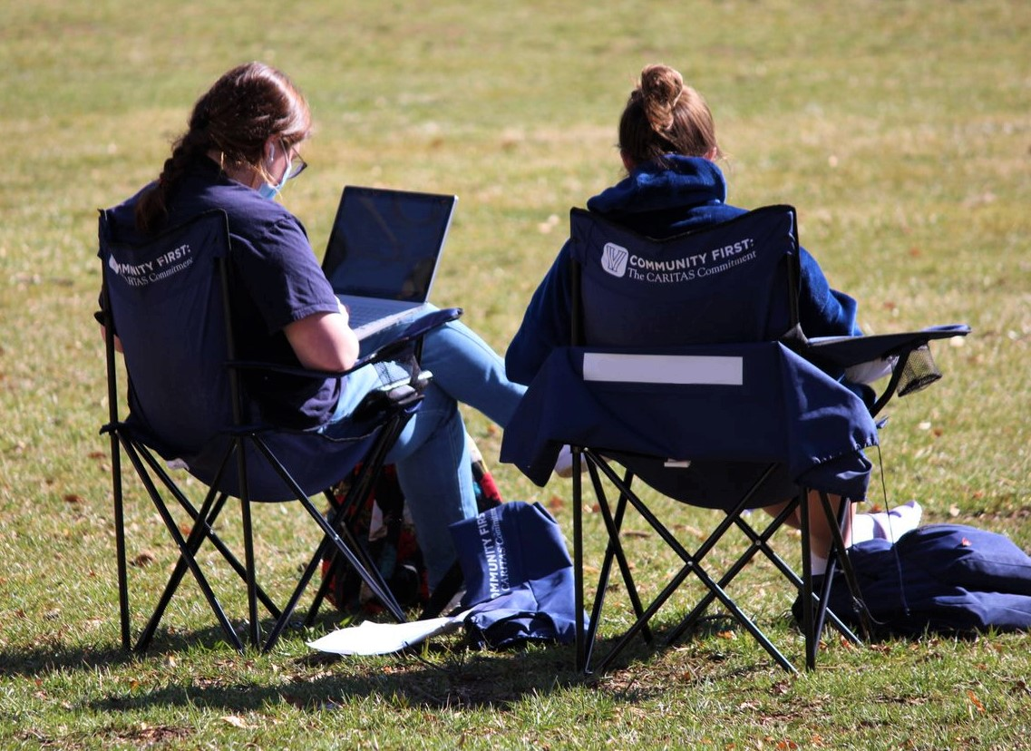 Photo of two student studying on the campus green.