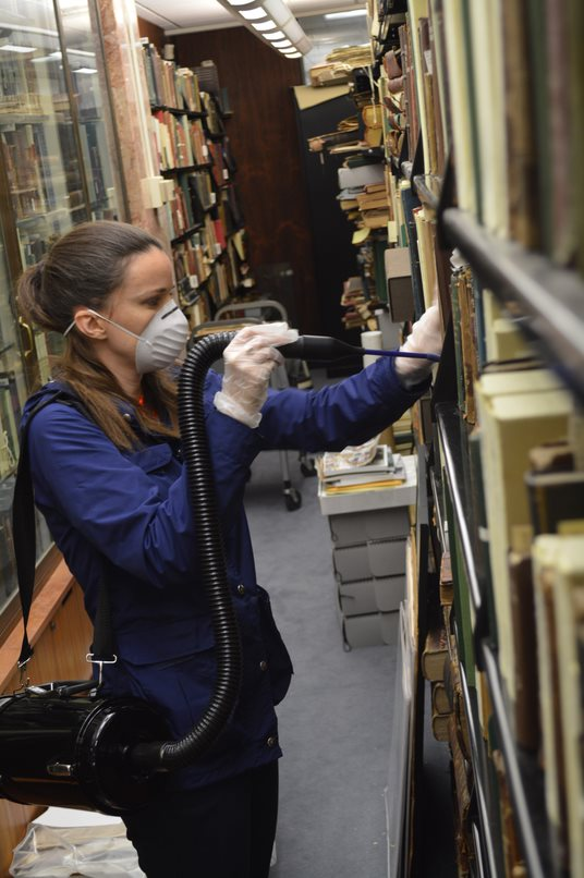 Beaudry Rae Allen '13 MA, Preservation and Digital Archivist, removes dust from books in Falvey Memorial Library's Special Collections.