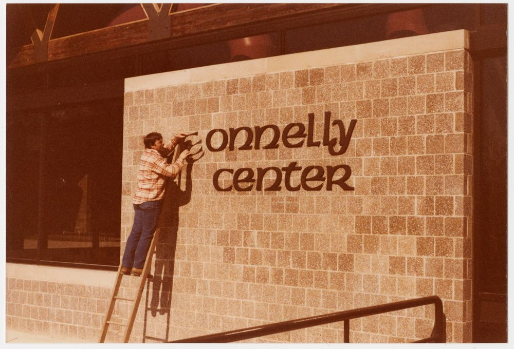 Installation of signage outside Connelly Center, May 1980.