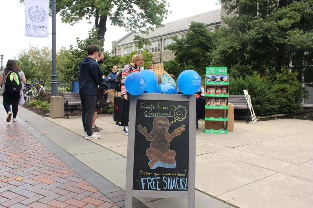 Library staff greet students in front of the library at Falvey's pop-up stressbusting event.
